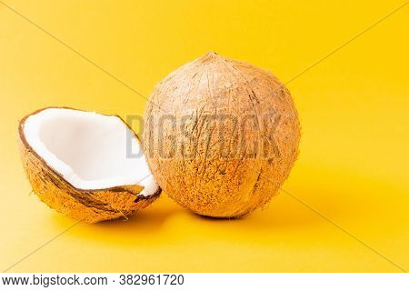Happy Coconuts Day Concept, Fresh Full Coconut With Half Coconut, Studio Shot Isolated On Yellow Bac