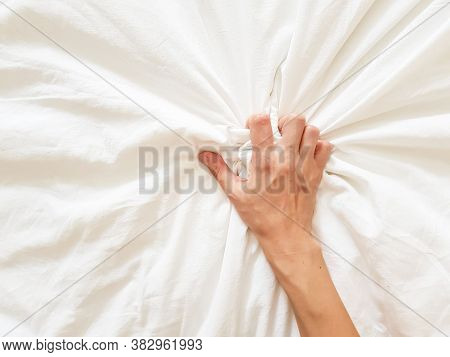 Close Up Sexy Woman Hand Pulling And Squeezing White Sheets In Ecstasy In Bed. Orgasm On White Bed.