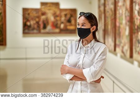 Girl Visitor Wearing An Antivirus Mask Standing Near Pictures In Museum Of Arts