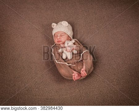 Newborn Baby In A Hat With Ears And A Teddy Bear In Hands On A Brown Background