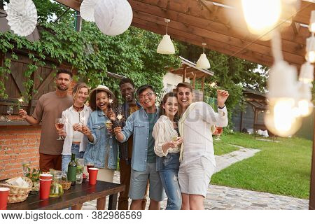 Multi-ethnic Group Of Friends Looking At Camera And Holding Sparklers While Enjoying Summer Party Ou