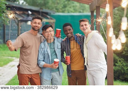 Multi-ethnic Group Of Male Friends Looking At Camera And Holding Sparklers While Enjoying Party Outd