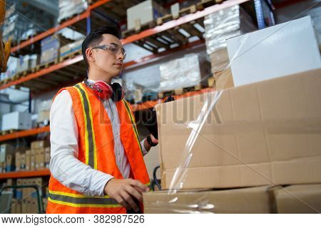 Young Man Working In A Warehouse With Boxes