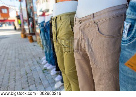 Various Trousers Weared On Model Dolls In Front Of A Pants Shop