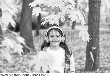 Falling Leaves. Happy Little Girl Wear Headphones Autumn Nature Background. Schoolgirl Listening Mod