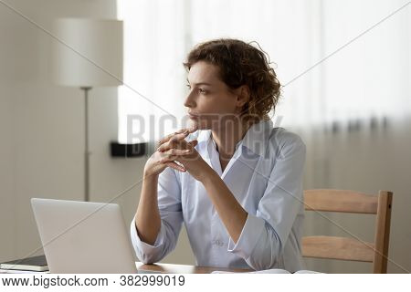 Thoughtful Woman Doctor Sitting At Work Desk, Pondering Problem Solution