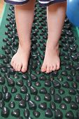 Children Caucasian feet standing on massage carpet poster