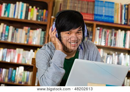 Student - Young Asian man in library with laptop and headphones learning