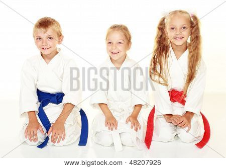 Cheerful young athletes in kimono sitting in a karate pose ritual