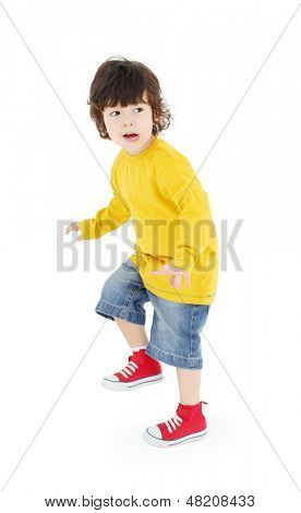 Little boy in yellow shirt stands and warily looks away isolated on white background.