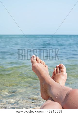 Female Legs Over Sea Waves And Sky