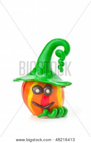 a handmade modeling clay pumpkin figure on a white background