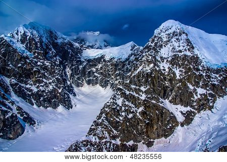 Blue Ice Glacier Headwaters and Snow-pack on Craggy Mountain Peaks with Dark Ominous Clouds