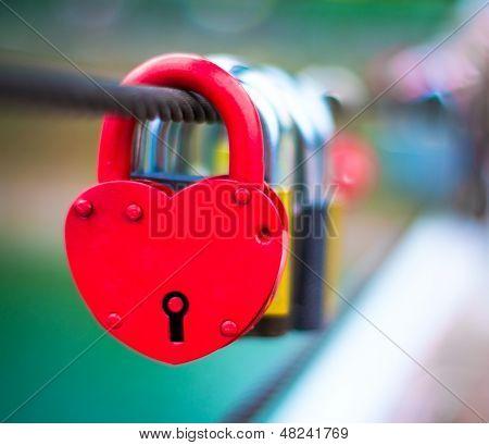 Red Lock in hart shape on rope bridge