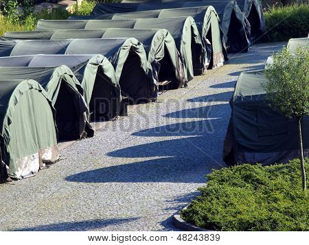 several large military tents on the paved area as a camp for youth poster