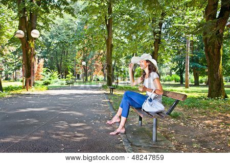 Beautiful young woman sitting on the bench in park in Mataruska banja, Serbia.