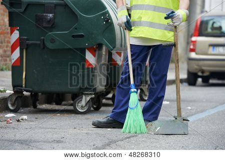 Process of urban street cleaning sweeping. Worker with broom and dust pan