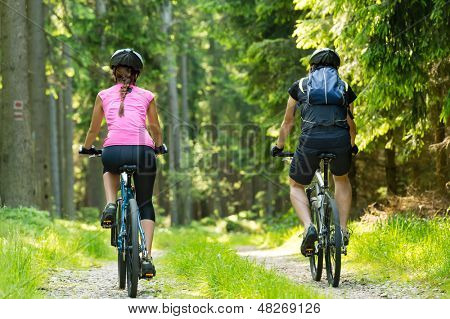 Bikers in forest cycling on track from behind