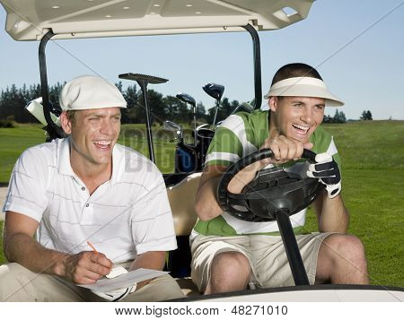 Cheerful young male golfers sitting in golf cart at course