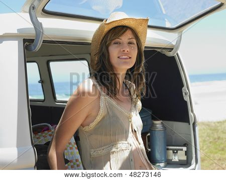 Portrait of young woman leaning on open tailgate of van at beach