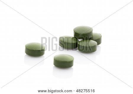 Verde pocas píldoras Isolaed sobre fondo blanco.