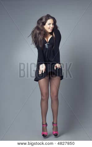 Happy model in stylish dress jumping in the studio poster