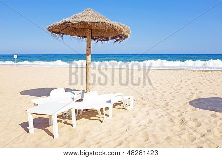 Thatched umbrella and beach chairs on the beach near Lagos Portugal