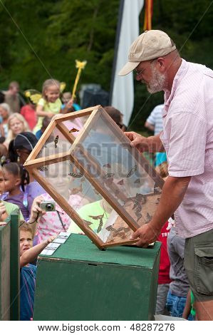 Hombre lanza mariposas como reloj de espectadores en el Festival de verano