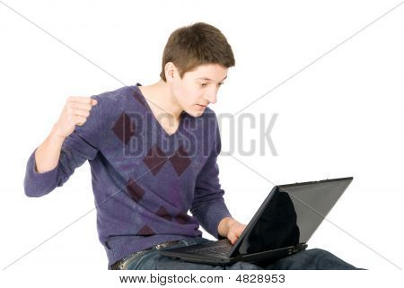 Young Man Is Angry About What He Sees On His Laptop And Going To Hit Notebook. Isolated Over White.