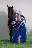 Woman in royal baroque dress standing next to a horse in the fog poster