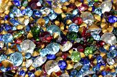 Extreme closeup of loose vintage rhinestones in a variety of colors and sizes. poster