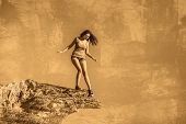 acrophobia woman tall stands on top of a rock cliff edge and is fearful horror poster