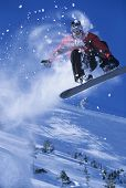 Low angle view of a snowboarder in midair with snow powder trailing behind above ski slope poster
