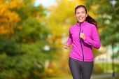 Female jogger. Fit young Asian woman jogging in park smiling happy running and enjoying a healthy outdoor lifestyle. Fitness runner girl in autumn forest with fall foliage. Mixed race Asian Caucasian. poster