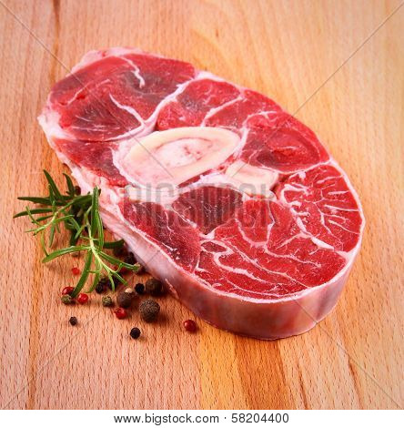 Fresh veal shank meat with herb on wood background top view poster