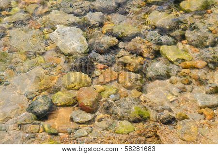 Water Ripples On The Shallow. Sea Pebbles Abstract Texture