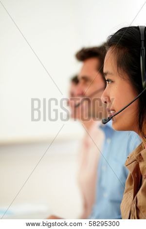 Portrait of young attractive callcenter people using earphone while smiling and sitting on workplace poster