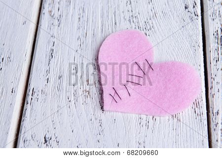 Broken heart and thread on wooden background