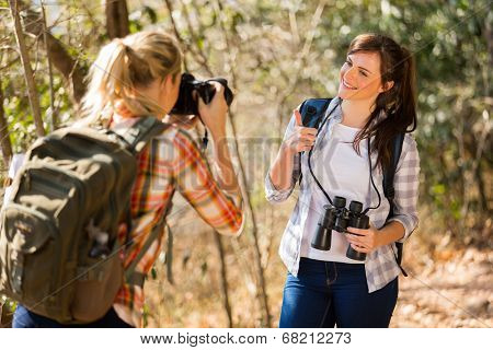 young woman taking photos of her friends in autumn forest