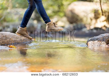 young woman hiking in mountain crossing stream poster