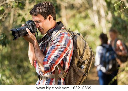 young man taking photos with dslr camera during hiking with friends