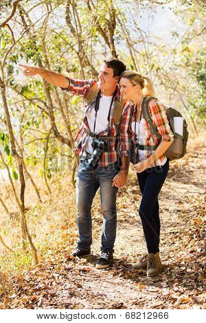 happy young couple mountain climbing together