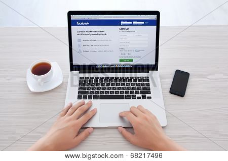 Man Sitting At The Macbook Retina With Site Facebook On The Screen
