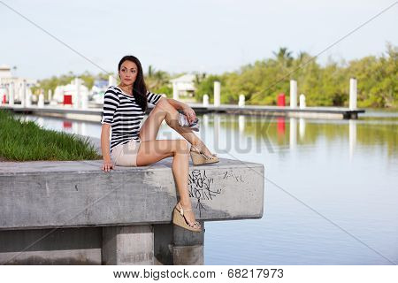 Attractive young female sitting on the ledge by the water