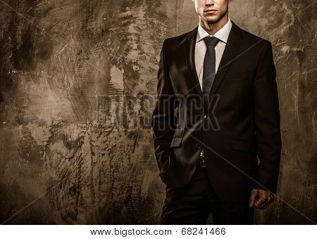 Well-dressed man in black suit against grunge wall