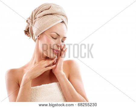 Spa Woman. Beautiful Girl After Bath Touching Her Face. Perfect Skin. Skincare. Young Skin. Beauty lady with towel on her headtouching her soft skin. Pampering. Treatment