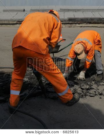 Two Workers With Bore On The Road