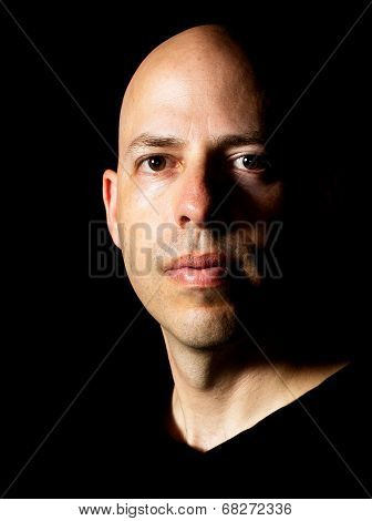 Low-key Rembrandt lighting portrait of a 40 year old bald man on black background poster