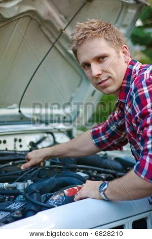 Young Man Working Under Car Hood