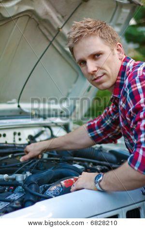 Jonge Man werken onder auto Hood